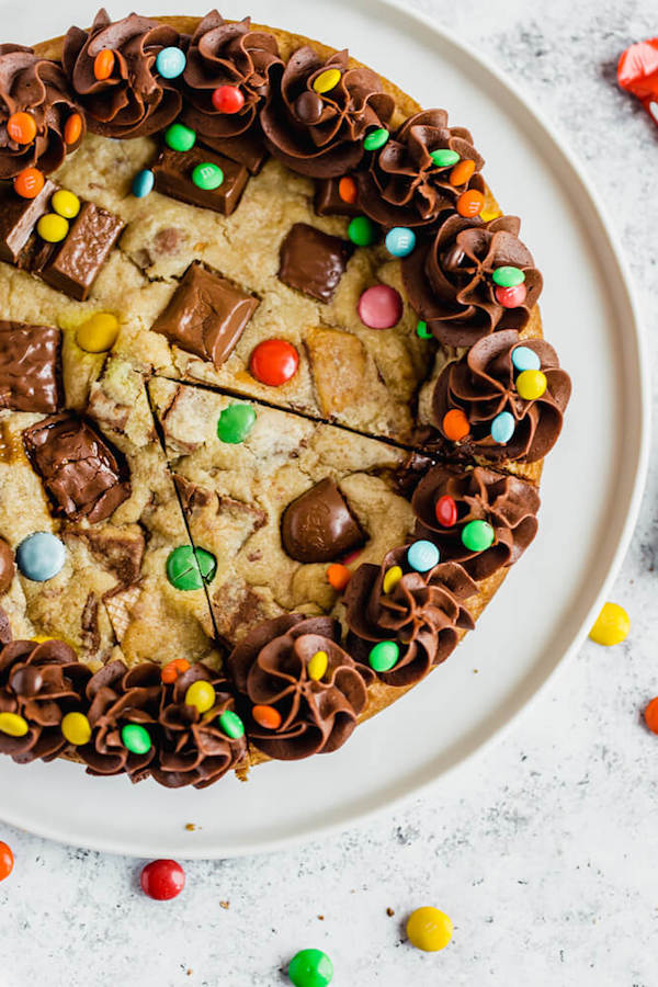 cookie cake loaded with halloween candy and topped with chocolate buttercream