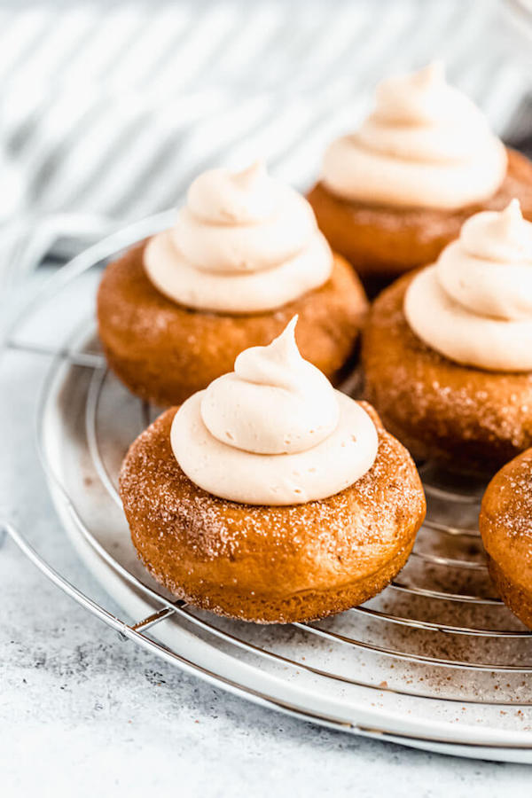 pumpkin donuts topped with salted caramel cream cheese frosting on a round wire rack
