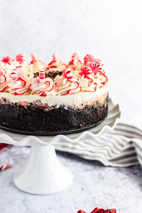 side view of white chocolate peppermint cheesecake on white cake stand