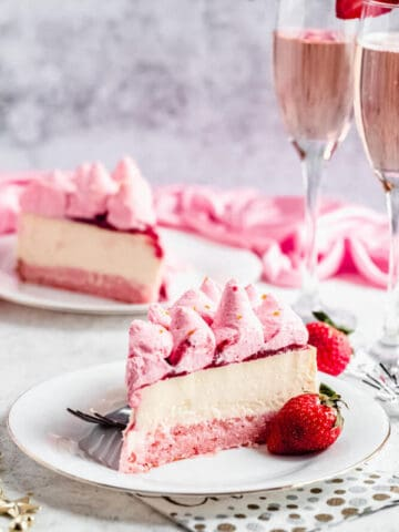 slice of champagne cheesecake on a white plate with a strawberry on the side