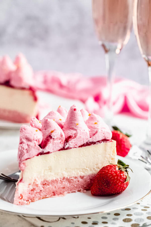 slice of pink and white champagne strawberry cheesecake on a white plate
