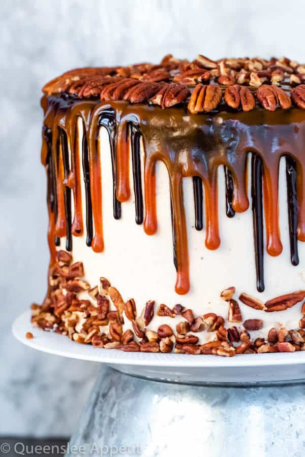 This Turtle Chocolate Layer Cake starts with rich, decadent and moist chocolate cake layers that are filled with a caramel pecan sauce and covered in a smooth caramel frosting, then finished off with a caramel and ganache drip and chopped pecans! | queensleeappetit.com