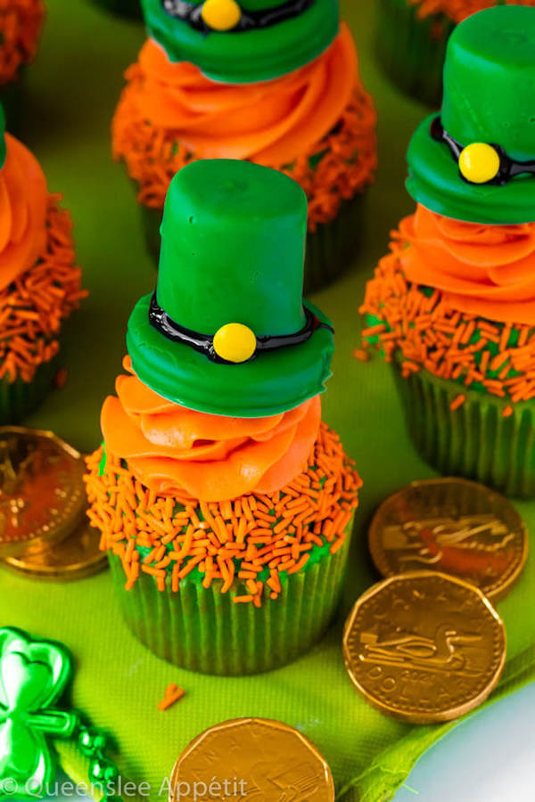 These Leprechaun Hat Cupcakes are super adorable and fun to make! A moist green vanilla cupcake stuffed with gold sprinkles, topped with a fluffy green and orange vanilla frosting and a cute little leprechaun hat sitting on top! This is the ultimate St. Patrick's Day treat!