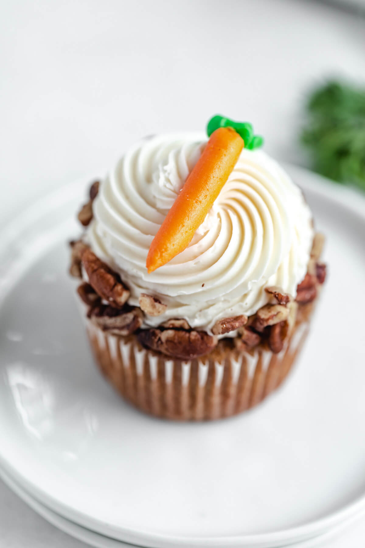 top angled close up of one cupcake on two white appetizer plates