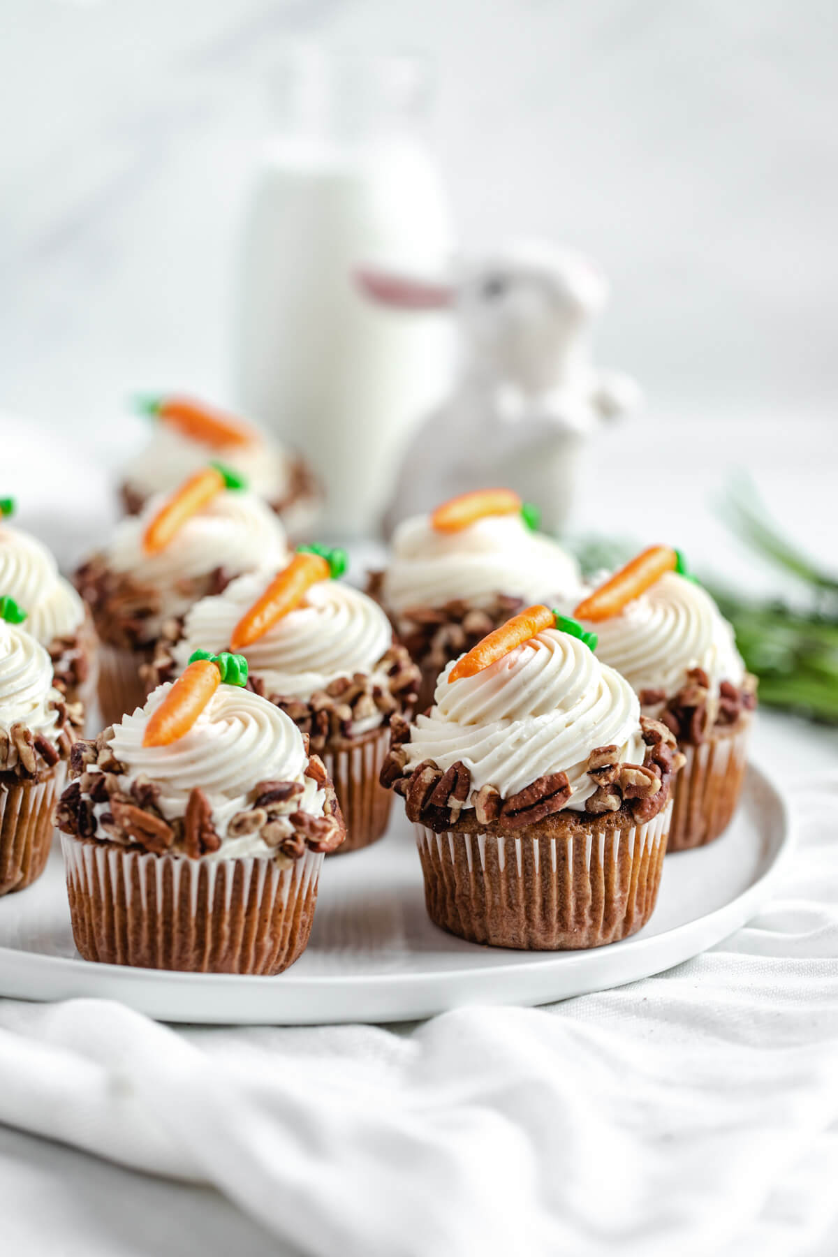 cupcakes on a white plate with carrots on top