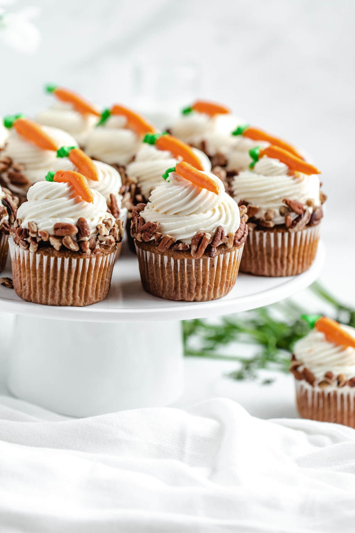 carrot cupcakes on a white cake stand