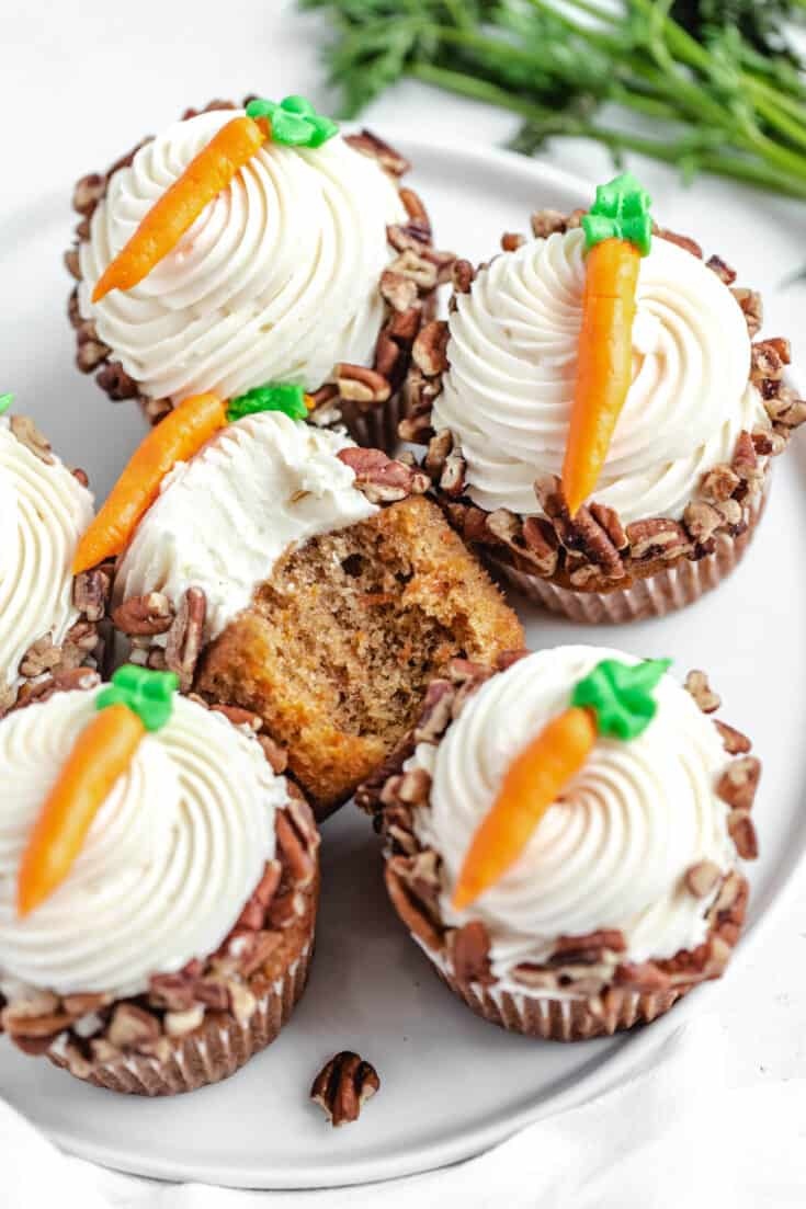 These Carrot Cake Cupcakes are to die for! A moist and tender carrot cake cupcake made with loads of fresh carrots, topped with silky cream cheese frosting and dipped in chopped pecans for extra crunch! | queensleeappetit.com #carrots #carrotcake #carrotcupcakes #easterrecipes #cupcakes