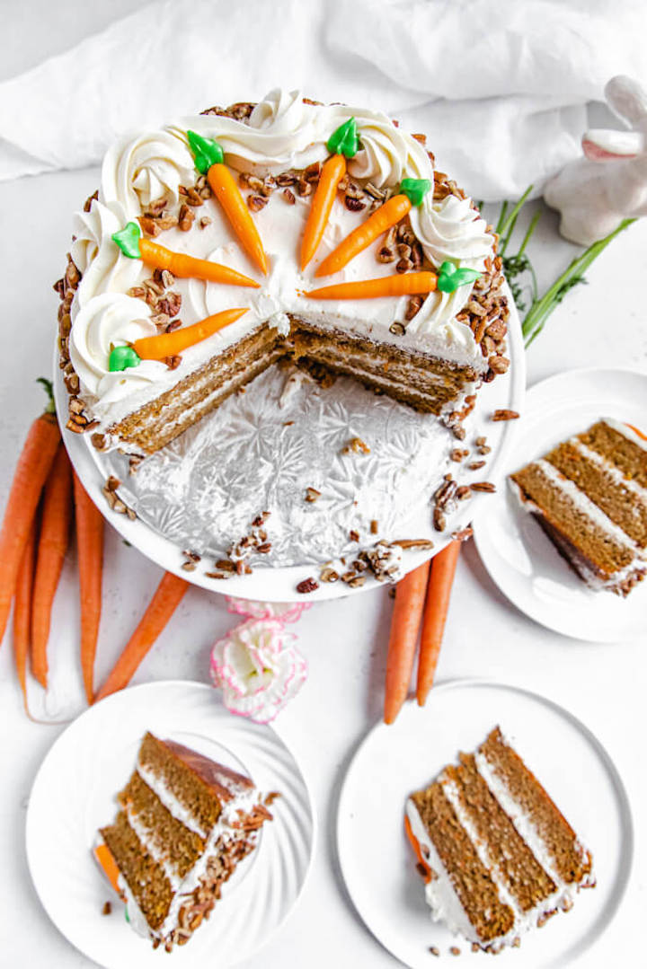 top view of sliced carrot cake with three slices on white plates