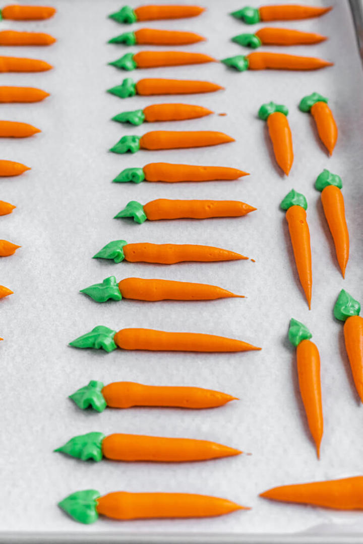 frosting carrots on parchment paper