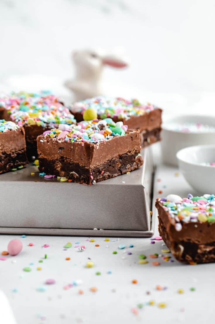 These Malted Milk Chocolate Easter Egg Fudge Brownies start with a rich and fudgy malted chocolate brownie that's loaded with mini easter eggs and chocolate chips. Sitting on top of the brownie is a creamy malted chocolate fudge topped with a ton of fun and colourful Easter goodies! | queensleeappetit.com #brownies #fudge #dessertideas