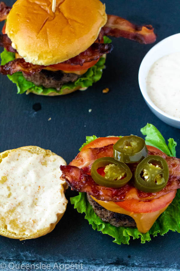 beer burgers with beer cheese sauce, fresh lettuce, tomatoes, crispy bacon, jalapeños and spicy aioli