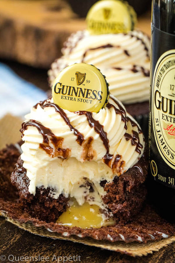 Guinness Chocolate Cupcakes with Baileys Buttercream Frosting, Guinness ganache drizzle and beer bottle cap on top and a Baileys ganache filling