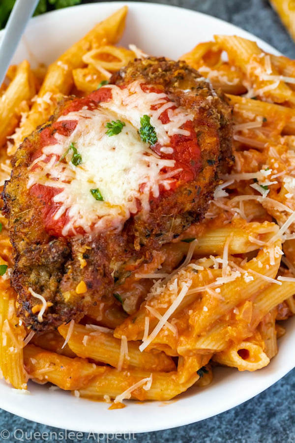 crispy chicken parmesan on a plate of penne alla vodka