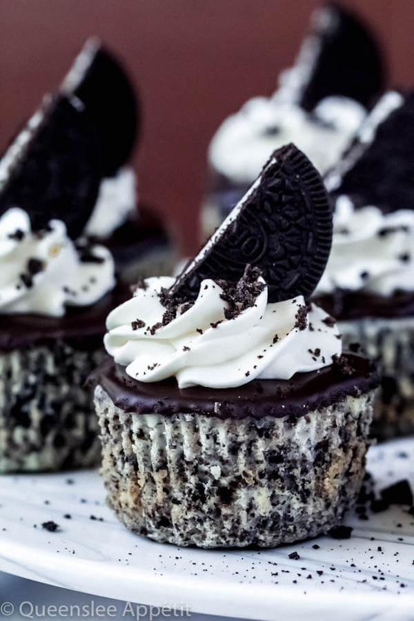 mini cookies and cream cheesecakes on a cake stand