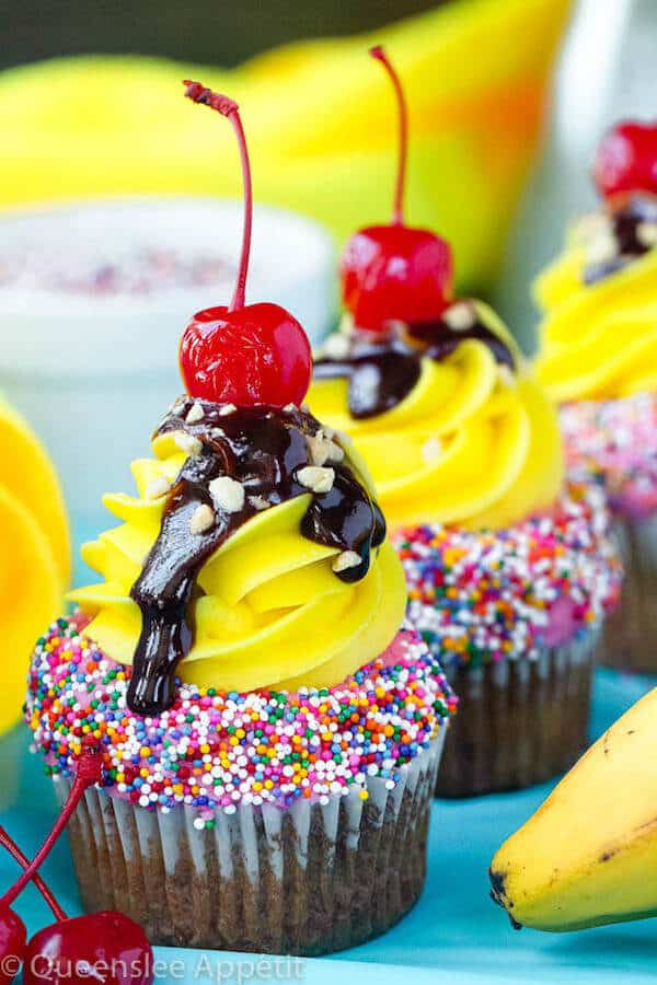 moist and delicious banana cupcake that's been decorated with strawberry and vanilla buttercream, colourful sprinkles, chocolate sauce, chopped nuts and a bright red cherry on top