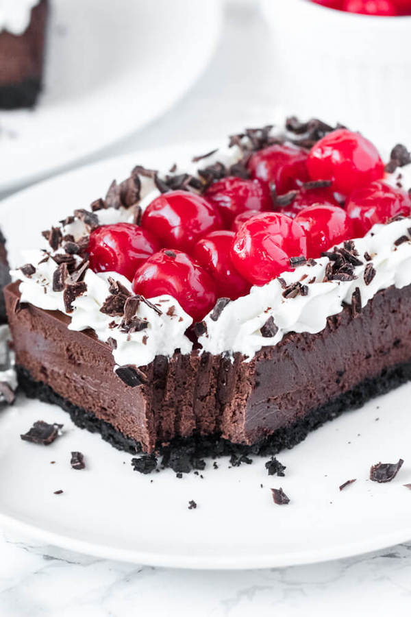 chocolate cheesecake bars with whipped cream, cherries and chocolate shavings