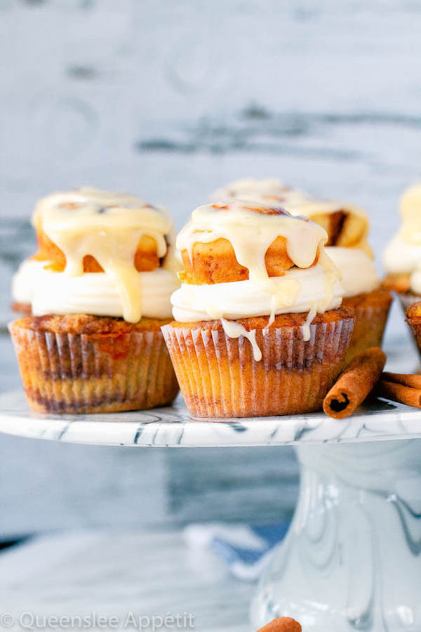 cinnamon roll cupcakes with cream cheese frosting and a glazed mini cinnamon roll on top