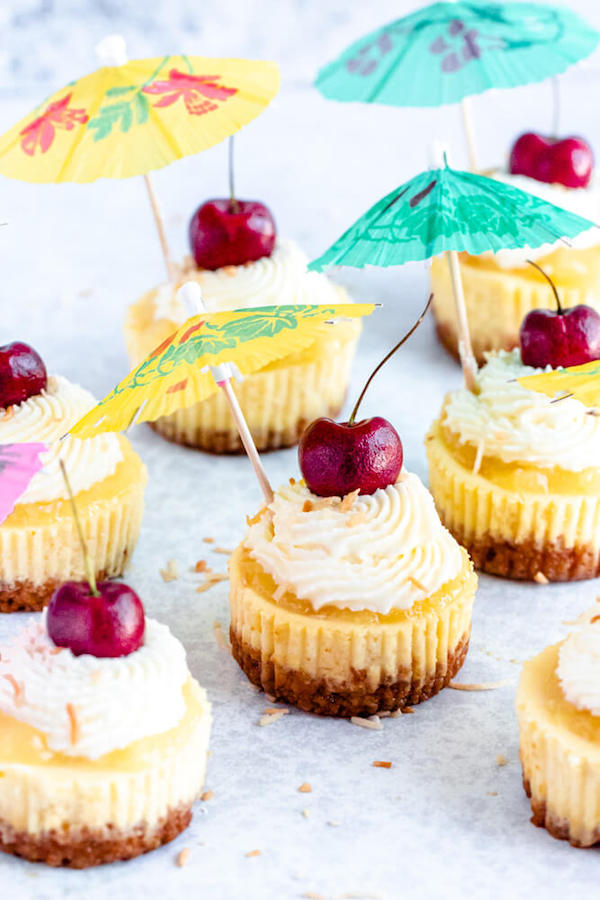 mini piña colada cheesecakes with pineapple sauce, coconut whipped cream, toasted coconut and a cherry on top.