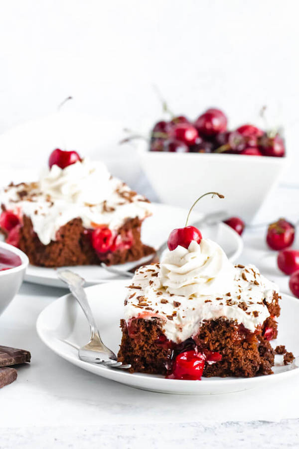 chocolate cake filled with cherry pie filling and topped with whipped cream, chocolate shavings and a cherry