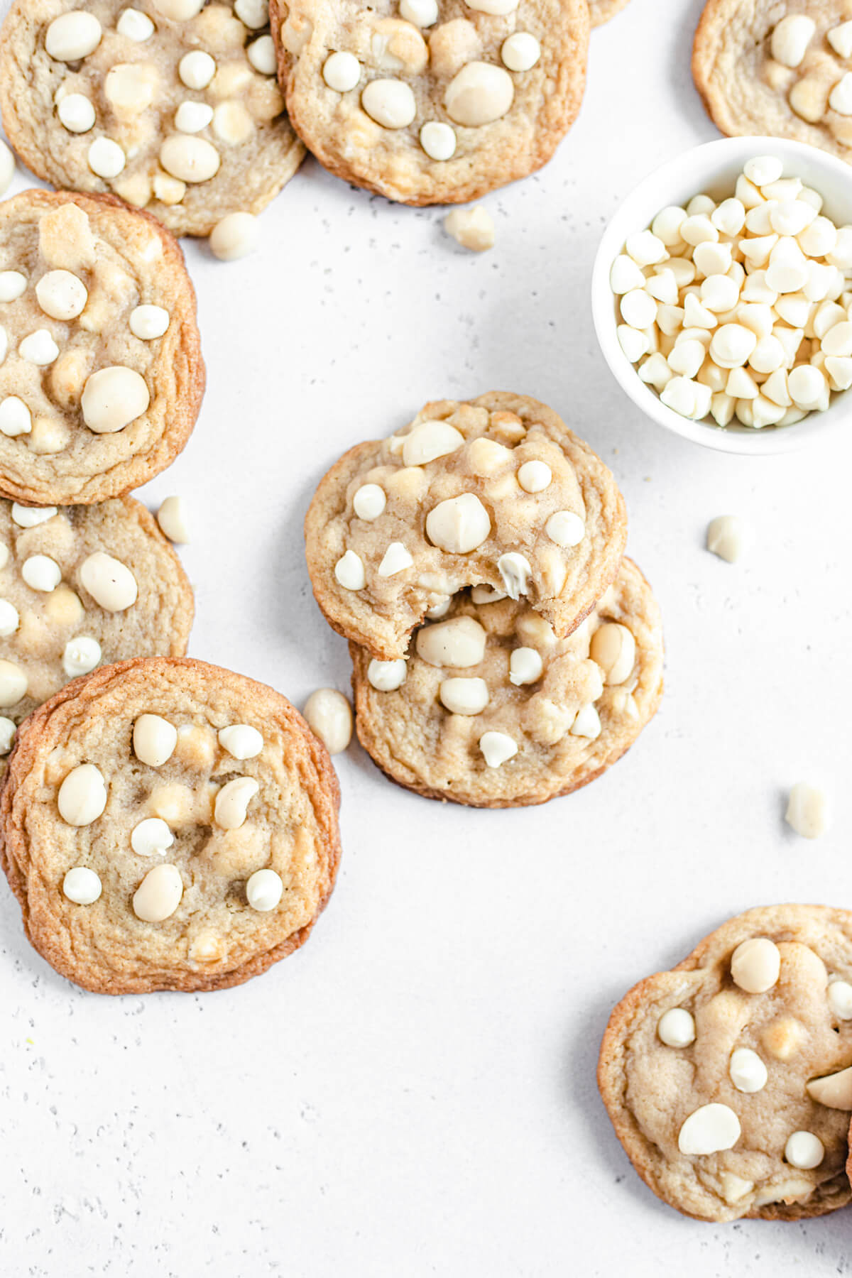 white chocolate and macadamia nut cookies with a bowl of white chocolate chips next to them