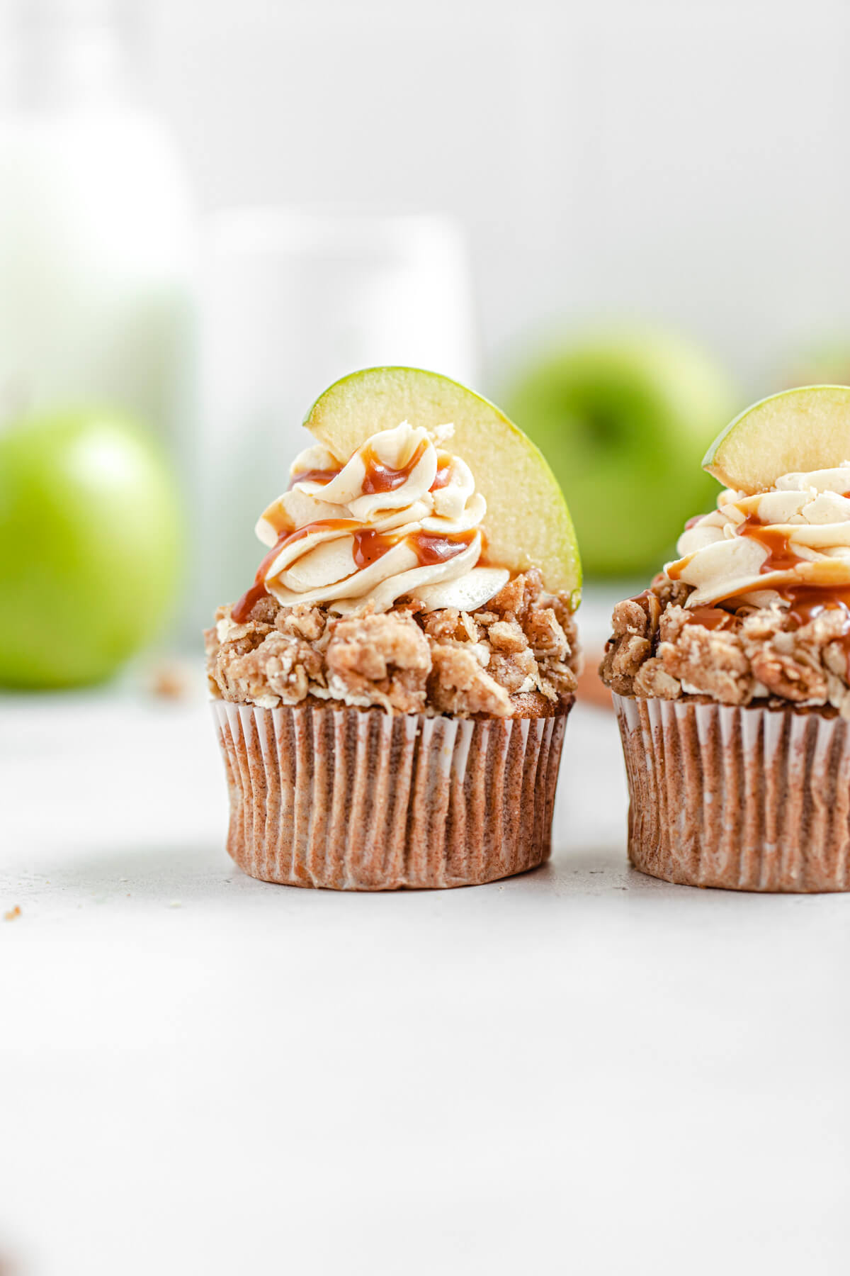 two cupcakes side by side with green apples in the background
