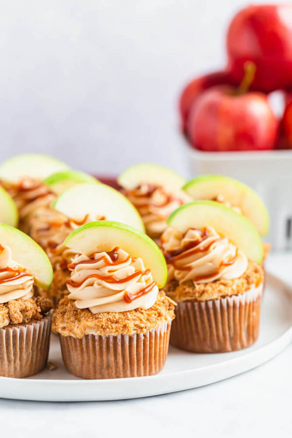 cinnamon apple cupcakes filled with homemade apple filling and topped with salted caramel cream cheese frosting and crumble topping