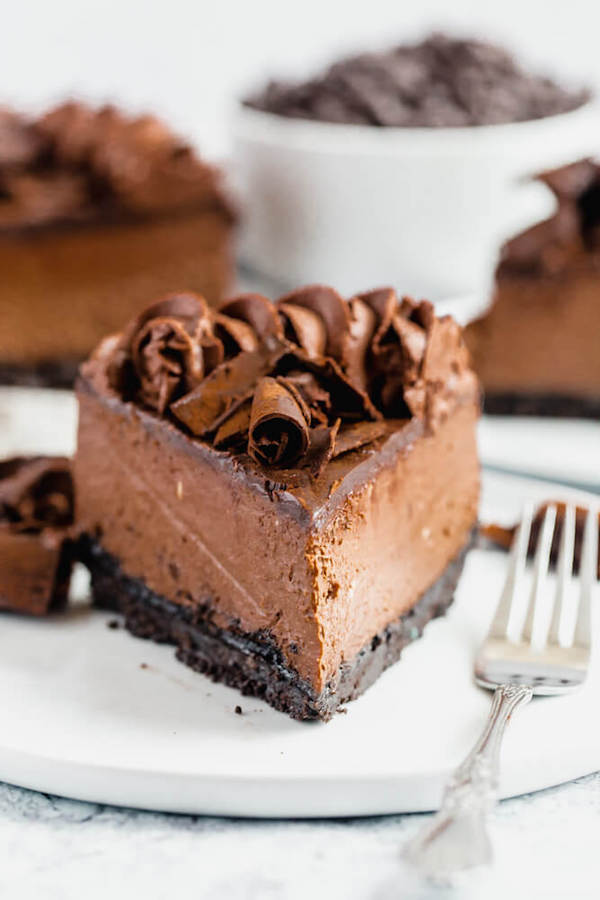 chocolate cheesecake baked in an Oreo crust topped with chocolate ganache, chocolate whipped cream, cocolate shards and a dust of cocoa powder.