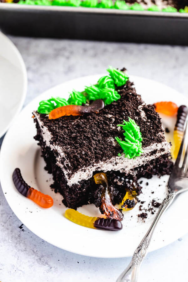 dark chocolate cake filled with chocolate pudding, Oreo crumbs, gummy worms and topped with Oreo cream cheese frosting, green grass buttercream and more Oreo crumbs and gummy worms