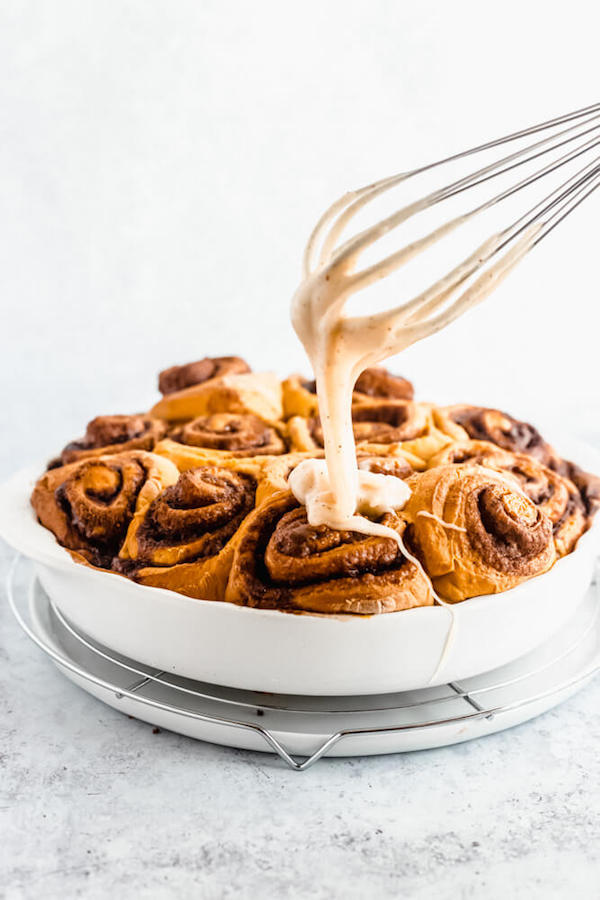 pouring browned butter cream cheese icing onto freshly baked pumpkin cinnamon rolls
