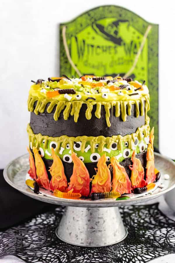 Dieser unglaubliche Hexenkessel-Kuchen besteht aus schwarzen und grünen Schokoladen- und Vanillekuchenschichten und einer dicken, grün getönten Vanillepuddingfüllung. Dieses unterhaltsame und einzigartige Dessert ist mit den gruseligen Zutaten des giftigen Gebräus einer Hexe überzogen, um Halloween zu feiern! #Cake #Cakedecorating #Cakerecipes #Cakedesign #Halloweentreats #Switchsbrew