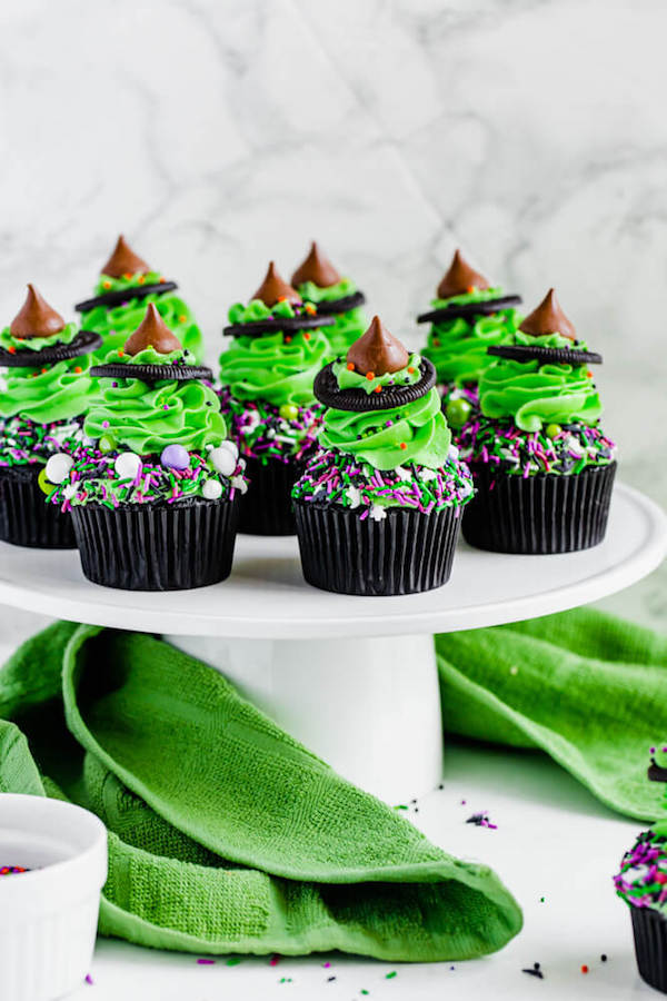 These Witch Hat Cupcakes are an easy Halloween dessert made with blacked out chocolate cupcakes, green tinted vanilla buttercream and a tasty witch's hat! This recipe can easily be doubled to serve at your next Halloween party!#cupcakes #halloween #halloweendesserts #witchhats