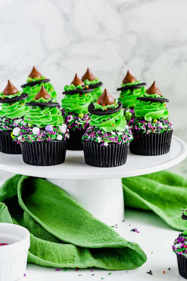 black chocolate cupcakes topped with green buttercream and witch hats