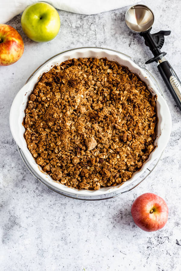 baked apple crisp surrounded by apples, spoons and an ice cream scoop