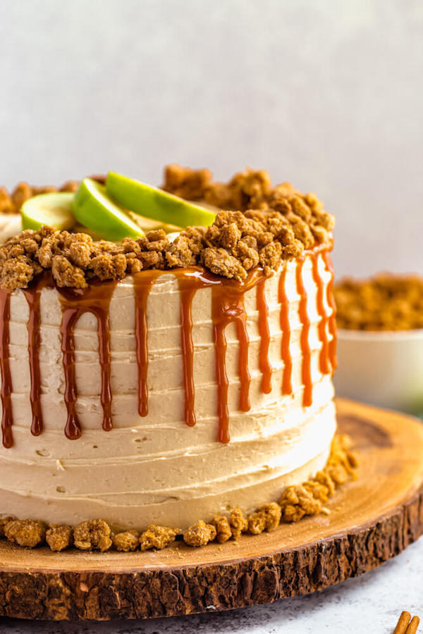 side view of caramel apple crumble cake on a wooden cake stand