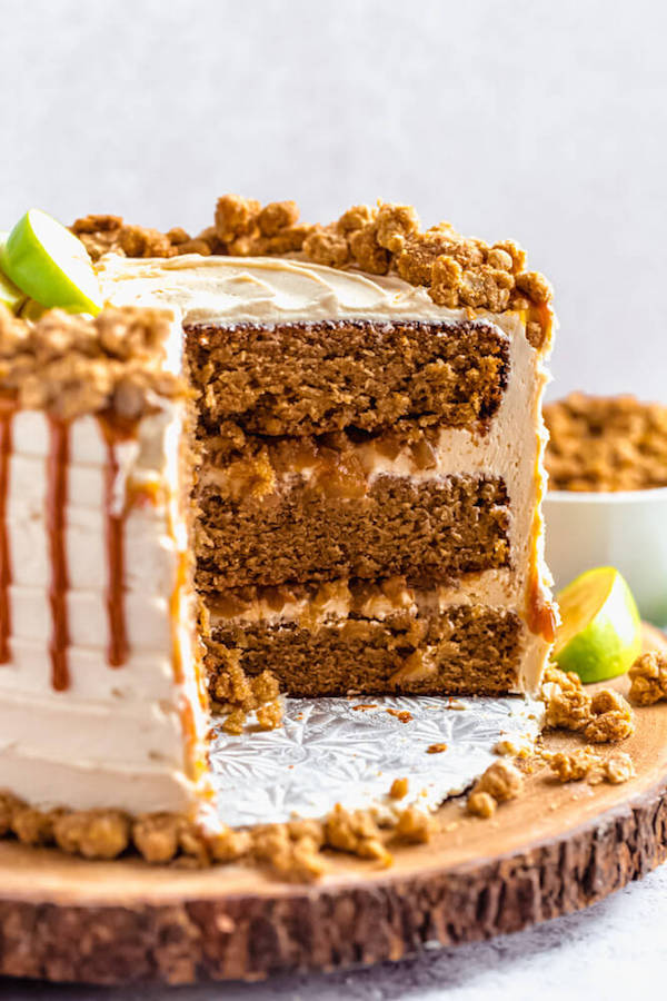 caramel apple crumble cake cut open on a wooden cake stand