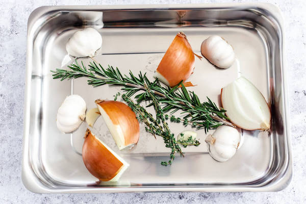 onion, garlic and herbs in a roasting pan
