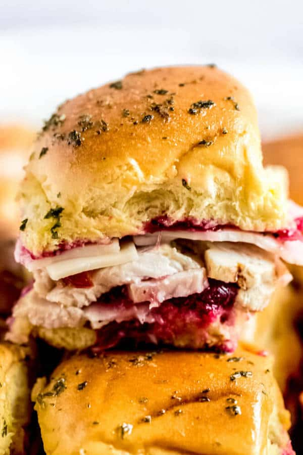 Grab an extra plate of Thanksgiving leftovers and make these easy Leftover Thanksgiving Turkey Cranberry Sliders. Made with fresh homemade cranberry sauce, sliced turkey breasts, crumbled bacon and swiss cheese, these sliders are a fun and simple way to enjoy the big days leftovers! | via. queensleeappetit.com #thanksgiving #thanksgivingappetizers #thanksgivingleftovers #sliders
