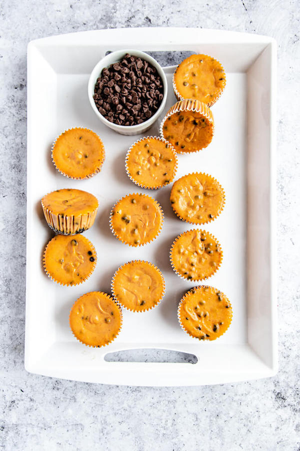 undecorated pumpkin cheesecakes on a white tray
