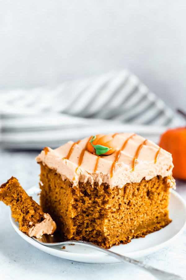 slice of pumpkin cake topped with caramel pumpkin spice cream cheese frosting
