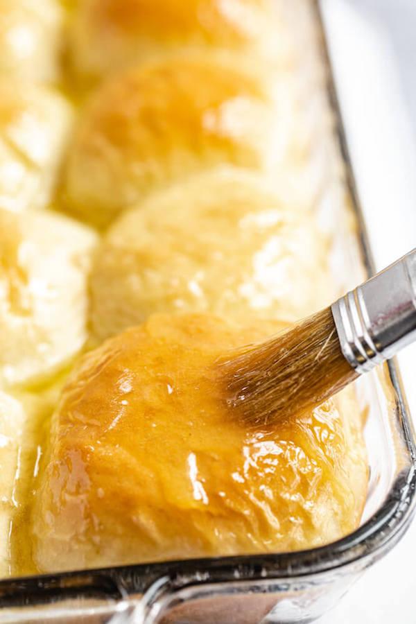 spreading honey butter onto dinner rolls