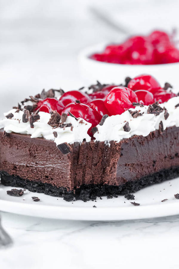 chocolate cheesecake bar topped with cherries on a white plate