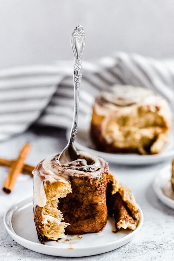fork stuck into the top of an unraveled cinnamon roll