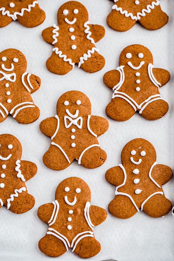 decorated gingerbread man holiday cookies on parchment paper