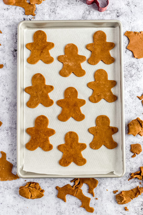 unbaked man shaped cookie dough on parchment lined baking sheet