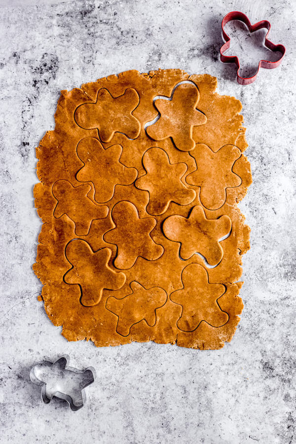 top view of rolled out gingerbread dough with man shaped cutouts