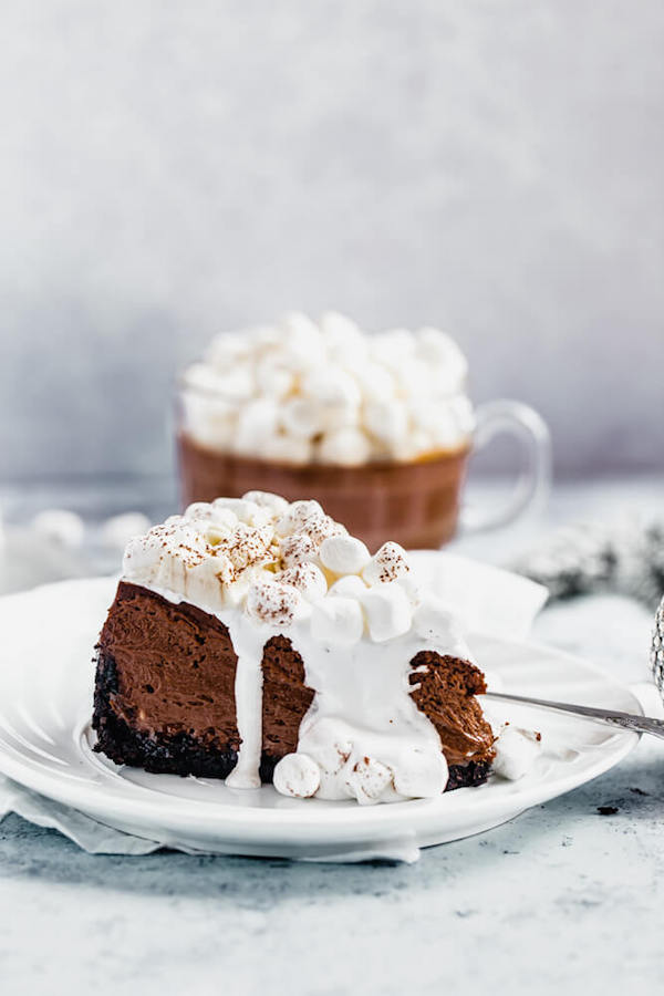 slice of hot chocolate flavoured cheesecake with marshmallow sauce on top and mug of hot chocolate in the back