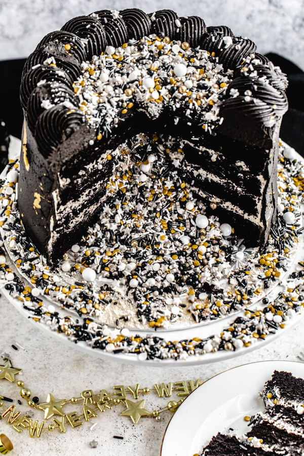 cake cut open with black, silver, gold and white sprinkles spilling out