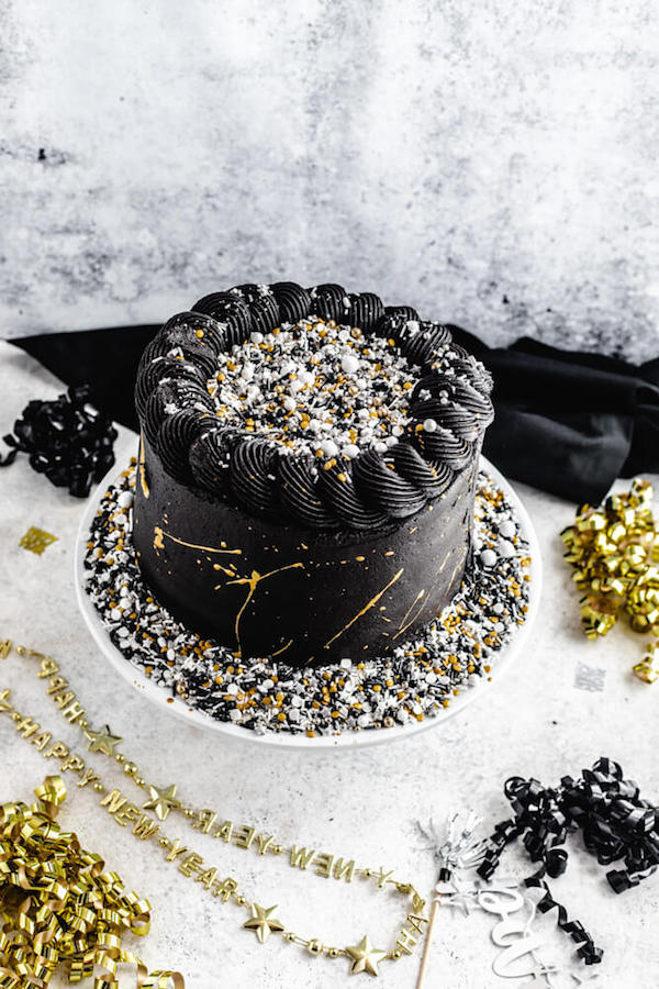 gold and black cake with sprinkles on top and around the bottom