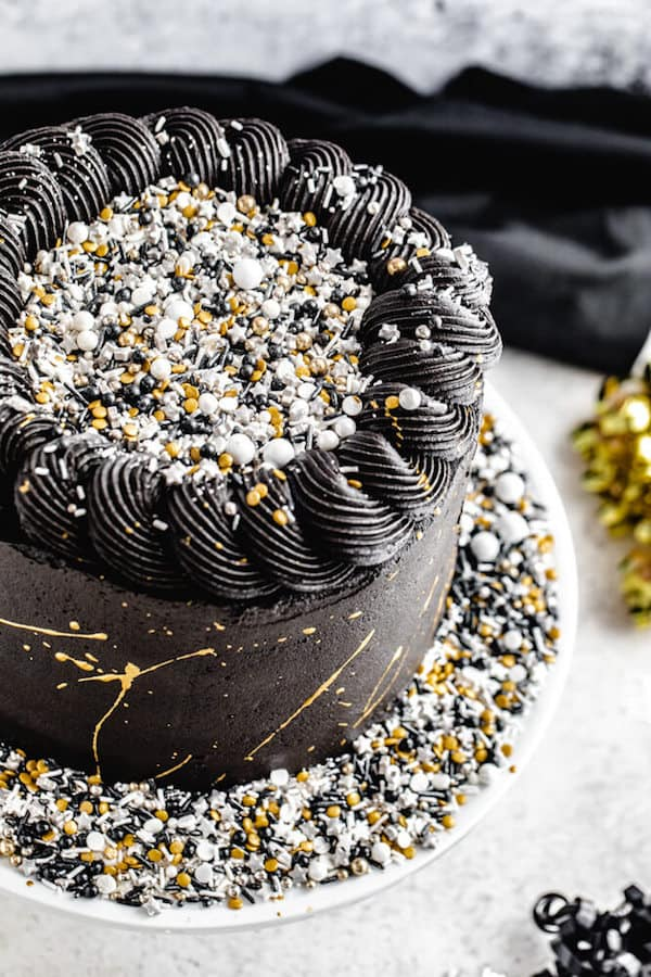 close up of black white silver and gold themed cake
