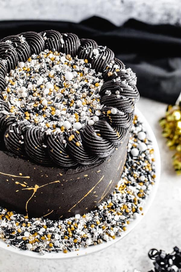 Beenden Sie das Jahr mit einem Knall! Der Silvesterparty-Kuchen ist eine Party von außen UND von innen! Wenn Sie in den köstlichen dunklen Schokoladenkuchen schneiden, fallen eine Menge funkelnder Streusel herunter. Das ist DER Festkuchen! | queensleeappetit.com #newyearseve #newyearseveparty #partyfood #dessert #cake